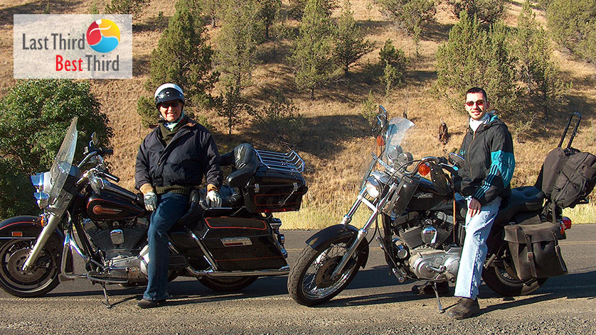 Father and son sit on their Harley Davidson motorcycles