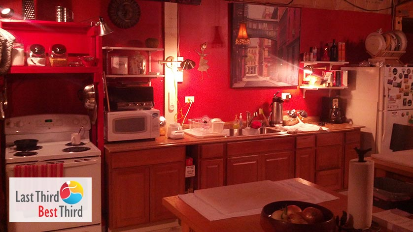 The dark red hue of a homey kitchen at night