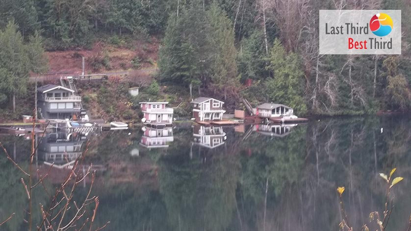 Four lake homes on a calm Lake Crescent with evergreen trees in the background