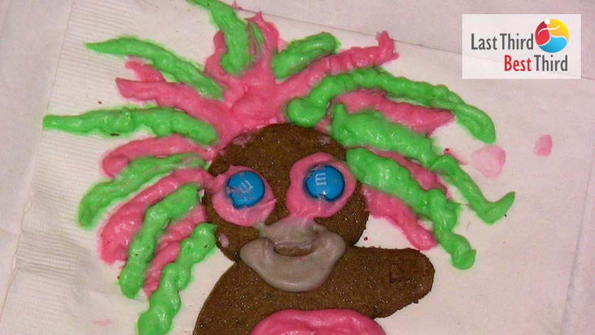 Gingerbread man with blue M&M candy eyes and pink and green dreadlocks