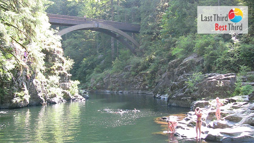Beach goers swim and prepare to swim in an Oregon river surrounded by lush greenery and high banks