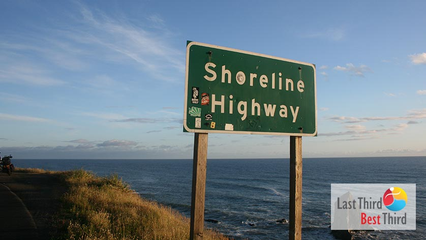 """Shoreline - Highway"" road sign on the side of a state road with Pacific Ocean in background"