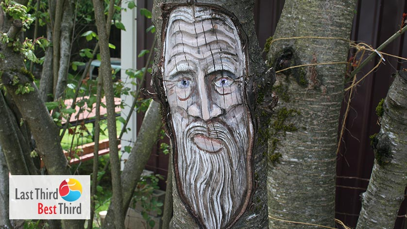 Carving of old mans face in the trunk of living tree.