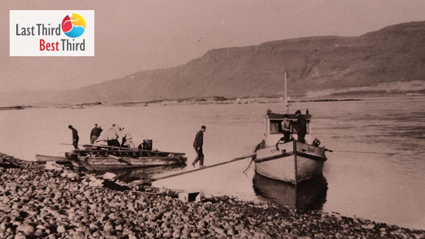 Vintage black and white photo of workers on two boats on rocky shore of river with mountains in the background.