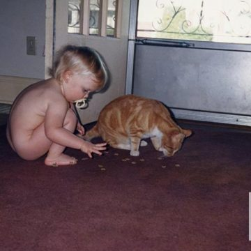 Adorable blonde baby with pacifier in front of front door feeding the orange tabby cat treats.