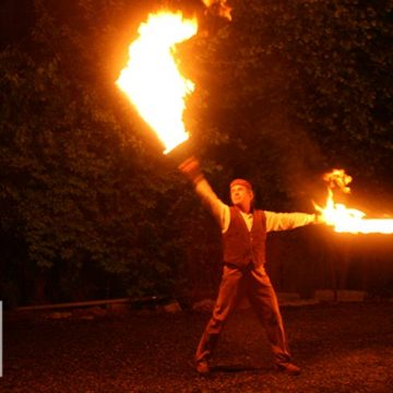 Man performing tricks with objects lit on fire.