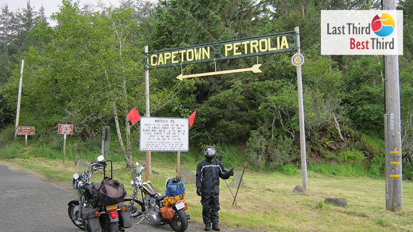 Motorcycles and cyclist standing in front of large sign to Capetown Petrolia.