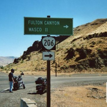 Route sign on paved road with motorcyclist and motorcycles with several mountain ranges in the background.