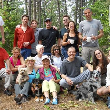Large group of friends and their dogs in a wooded area.