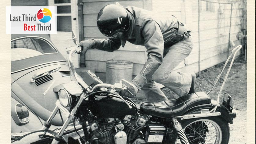 Black and white photo of man with helmet kick starting a motorcycle with older Volkswagen Beetle in the background.