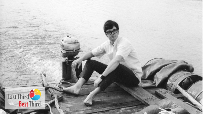 Black and white photo of young man on a raft boat with motor.