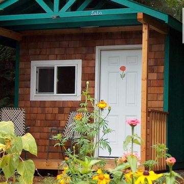 Wood shingled cabin with green and white trim in the forest surrounded by pine trees and flowers.