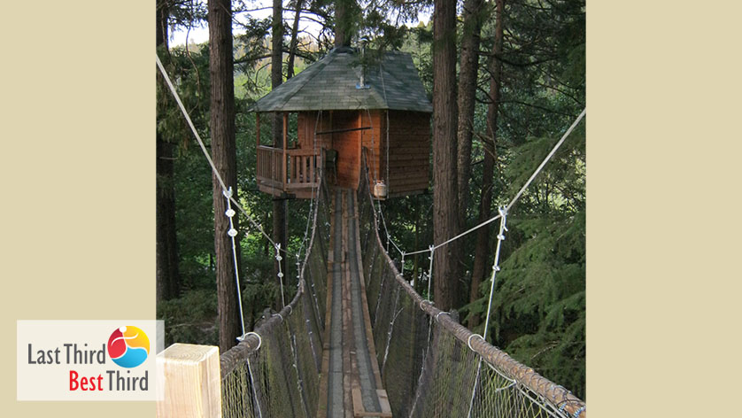 Rope bridge in the trees leading to treehouse in the woods.