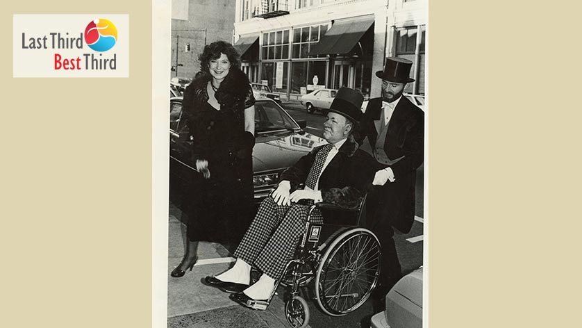Black and white photo of man and woman dressed in black tie attire pushing a well dressed gentleman in a wheelchair.