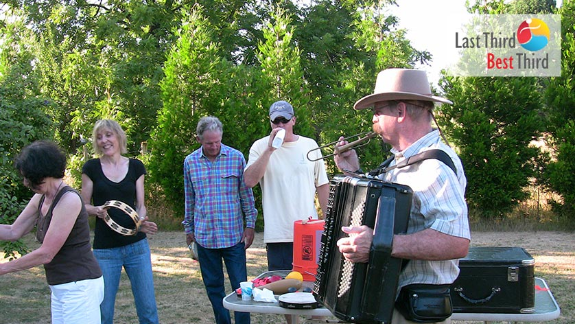 Group of musicians jamming together in a field surrounded by large green trees.
