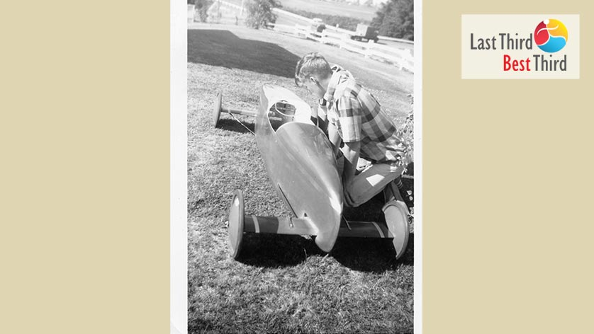 Black and white photo of a young man inspecting the work of a soapbox derby car in a yard with a large fence in the backyard.
