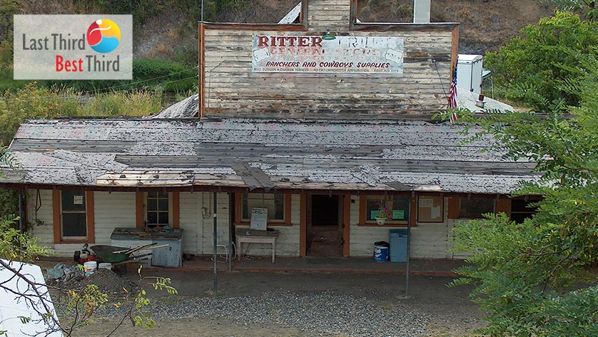 Old wood store with a rancher and cowboy supply sign on top and a front porch that spans the width of the building.
