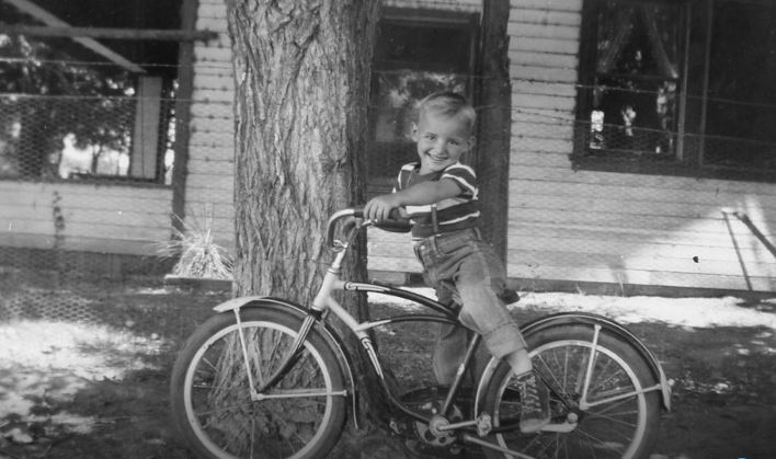 A 5-year-old, smiling RO on his bike in front of grandma's house