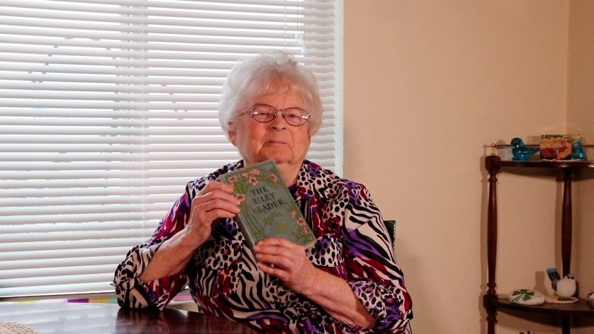 "Aunt Jean holding ""The Riley Reader"" book"