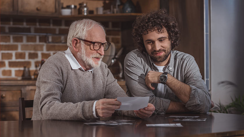 Senior Father sharing photos with Adult son