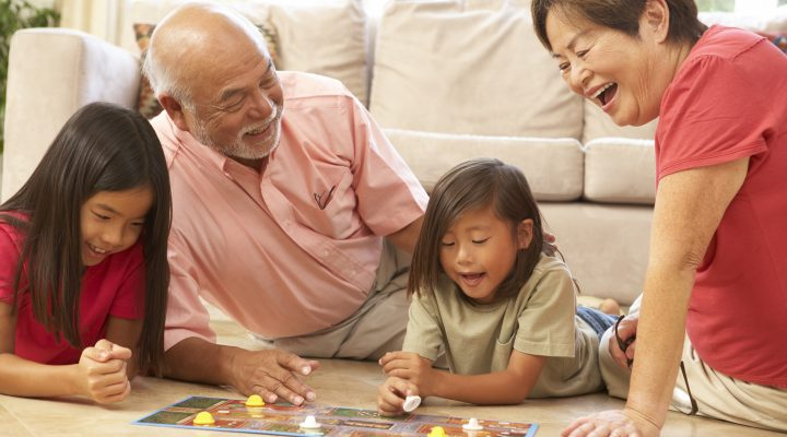 Japanese grandparents play board game with 2 grand daughters on living room floor